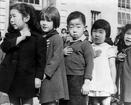 Dorothea Lange photo of Japanese American children reciting the Pledge of Allegiance before being sent to concentration camps.